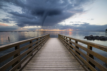 tornado on the sea with a pier in the foreground