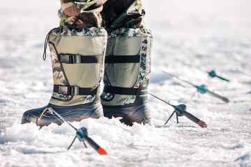 fisherman stands in boots on snow in the winter near fishing rods