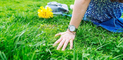 woman sitting on grass in city park with yellow flowers
