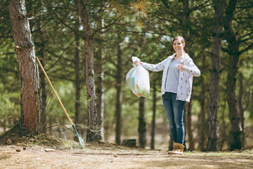 Young smiling woman cleaning rubbish holding trash bags and showing thumb up in park on green background. Problem of environmental pollution. Stop nature garbage, environment protection concept.