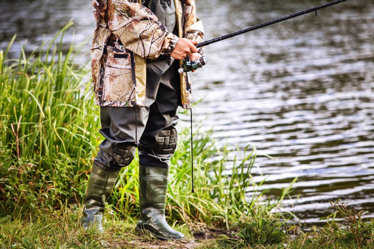 a man in military uniform and rubber boots is fishing on the river bank