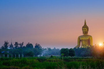 Deurstickers Biggest golden Buddha statue on the green field and sunset in Thailand at Wat Muang, Ang Thong Province, Thailand