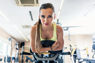 Low-angle view portrait of a cheerful and beautiful woman looking at camera, while holding the electronic display of a stationary bicycle during cycling workout at a trendy fitness club