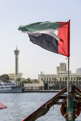 The UAE flag, flying the breeze, on Dubai Creek with the old district of Dubai, Bur Dubai, and a mosque minaret, in the background