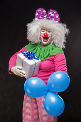 Funny clown with hair and a cheerful make-up holding a gift on a black background
