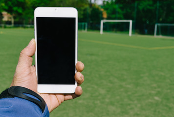 Man holding smart phone with copy space on football grass