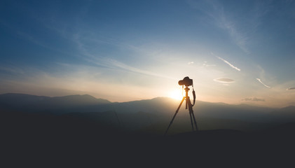 Silhouette of a camera on a tripod. Shooting sunset in the mountains