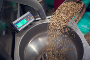 Image of scoop with non-roasted coffee beans, industrial scales