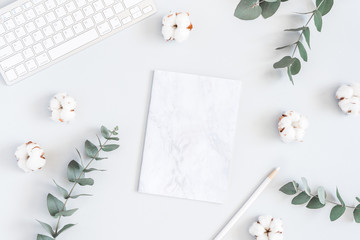 Workspace with computer, marble paper blank, cotton flowers and eucalyptus branches on pastel blue background. Flat lay, top view, copy space