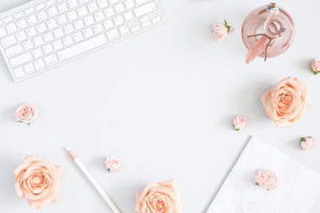 Feminine workspace with computer, rose flowers, marble paper blank. Flat lay, top view, copy space