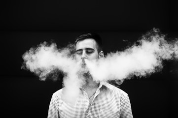 Vape man. Handsome young white guy with modern haircut in in checkered sleeveless shirt vaping an electronic cigarette opposite the futuristic urban background in the spring. Black and white.