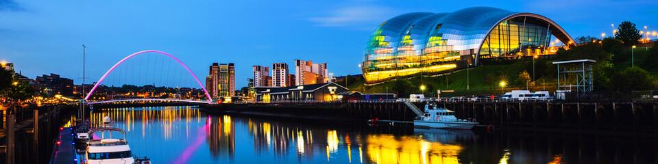 Famous Millennium bridge at night. Illuminated landmarks with river Tyne in Newcastle, UK