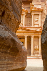 The facade of the Treasury (Al Khazneh) carved into the red rock, seen from the Siq, Petra, Jordan.