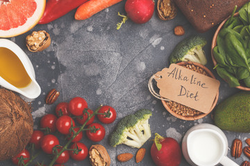 Healthy food background, trendy Alkaline diet products - fruits, vegetables, cereals, nuts, oil, dark background, top view