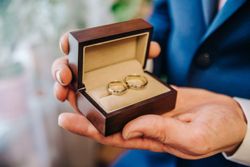the groom in his hands holds a beautiful box and two wedding rings in her