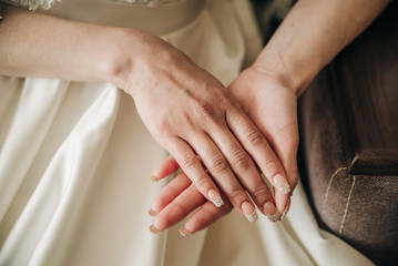 beautiful bride hands with a manicure lie on a dress