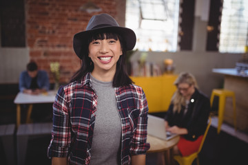 Smiling young woman wearing hat standing at coffee shop