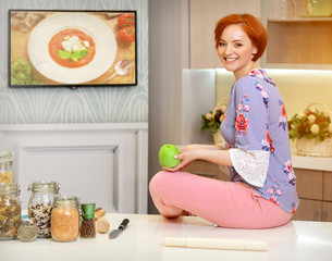 girl with ginger hair in the kitchen with apple
