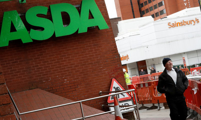 A man walks past branches of ASDA and Sainsbury's in Stockport.