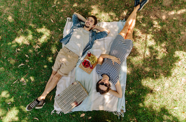 Couple relaxing on a picnic at park Wall mural