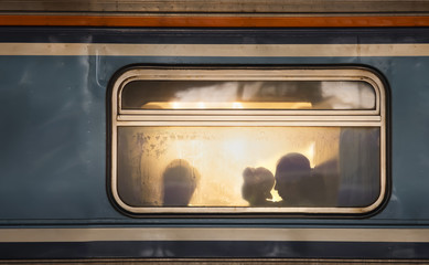 Silhouettes of passengers in old train wagon
