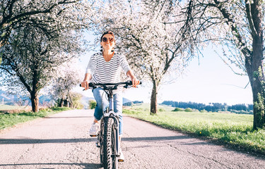 Happy smiling woman rides a bicycle on the country road under blossom trees