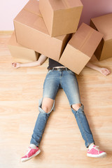 Image of woman in jeans lying under cardboard boxes