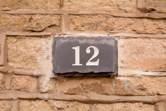 House number 12 sign on slate fixed to wall