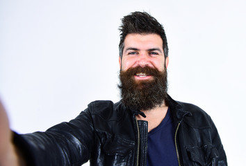Man with beard and mustache on smiling face looking at camera. Macho wears leather jacket, white background. Hipster looks happy and cheerful while taking selfie photo. Masculinity concept.