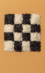 Black and white rice in checkerboard pattern on orange paper. Food background