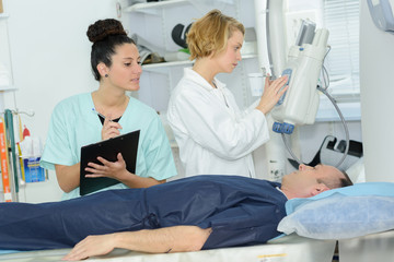 doctor looking at female patient going through ct scan