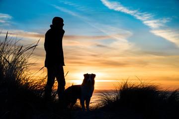 Silhouette von einem Mann und einen Hund am Strand bei Sonnenuntergang umrahmt von Gräsern.