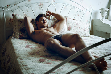 sexy and naked muscular young man posing on the bed