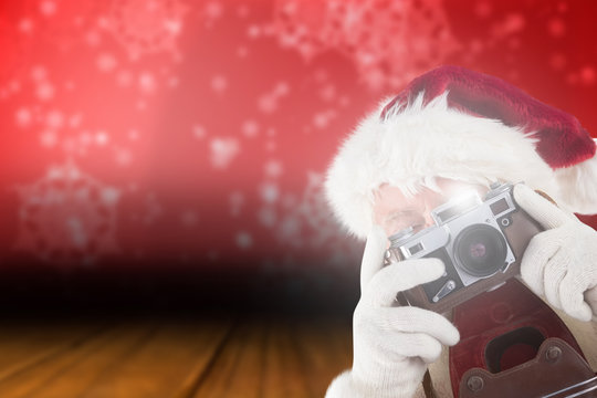 Santa is taking a picture against snowflake wallpaper over floor boards