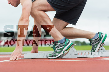 Side view of a man ready to race on running trac against stay motivated