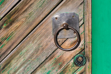 Old handle and padlock on a wooden door