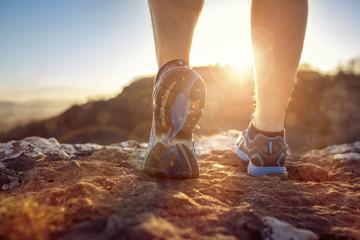 Runner feet running on trail looking at sunset