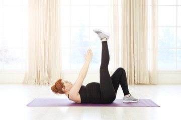Beautiful pregnant woman practicing prenatal yoga or pilates