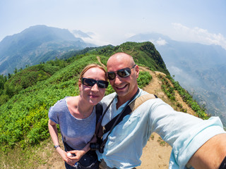 Caucasian couple makes selfie in the mountains near Sapa, Vietnam.
