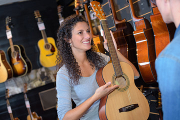 woman holding acoustic guitar at music store