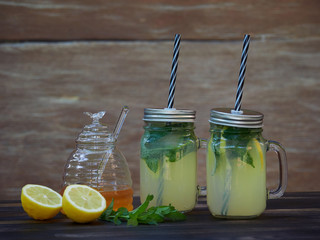 Two jars of fresh lemonade with sparkling water, mint and honey, set on a dark oak table, with brown wood background