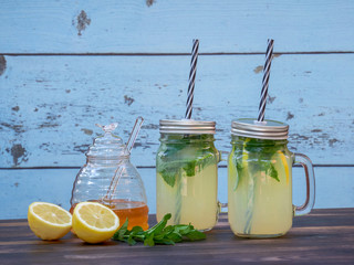 Two jars of fresh lemonade with sparkling water, mint and honey, set on a dark oak table, with a blue barn wall .in the background