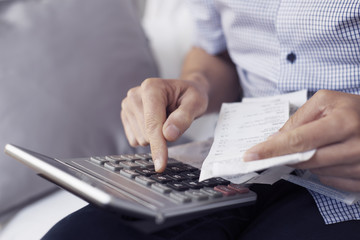 young man with bills and calculator