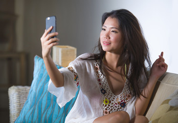young beautiful and happy Asian Chinese 20s or 30s woman taking selfie picture with mobile phone sitting at home living room sofa couch smiling