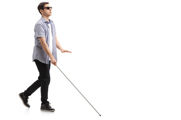 Blind young man with a cane walking