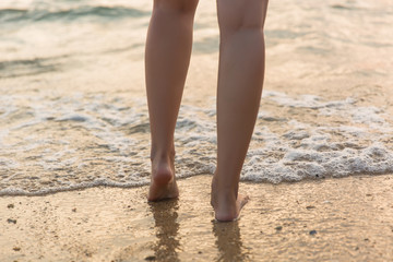 Closeup of a woman bare feet walking at a beach at sunset, with a wave foaming - travel and relaxing