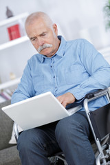 grandfather on wheelchair trying to use alone the internet