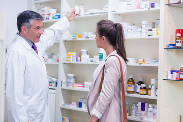 Pharmacist taking medicine in shelf