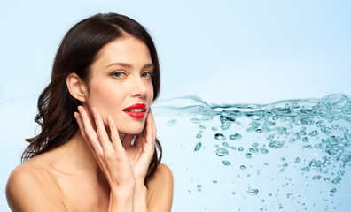 beauty, make up and skin moisturizing concept - happy smiling young woman with red lipstick touching her face over blue background and bubbles in water
