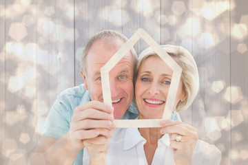 Happy older couple holding house shape against light glowing dots design pattern